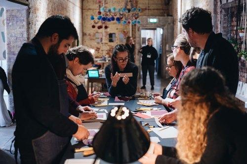 Group of people at London Craft Week doing book binding