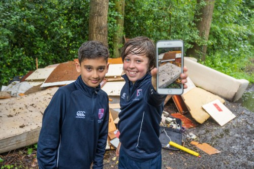 Two boys in front of a pile of rubbish