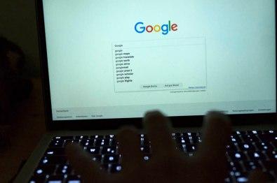 Eine Hand tippt auf einer Tastatur etwas bei Google ein