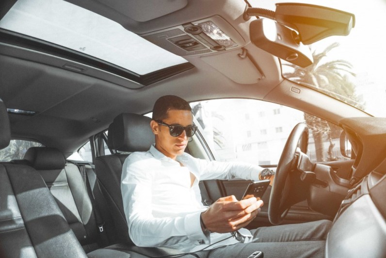 - checkingphone 1024x683 - Top 20 driving distractions. Four in five motorists admit taking eyes of the road to use phones, even stroke pets!