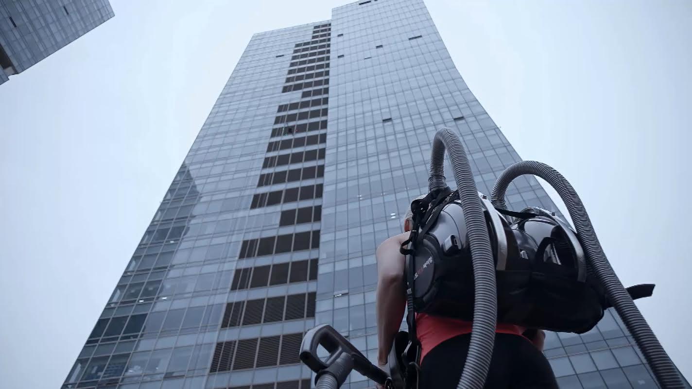 Uma alpinista usa 2 aspiradores a vácuo para escalar