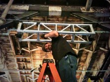 Topher rigging truss to hang a projector.