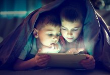 Two kids using tablet pc under blanket at night.