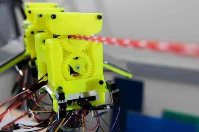 Image shows components of the SlothBot, which is powered by two photovoltaic panels. 3D-printed gears and switches help the robot switch from one cable to another./ Image: Georgia Tech
