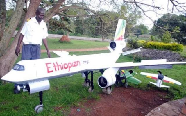 Mr Julius Otai poses with his locally made aeroplane