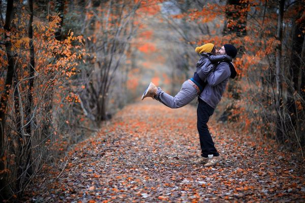 young people embracing in the autumn park