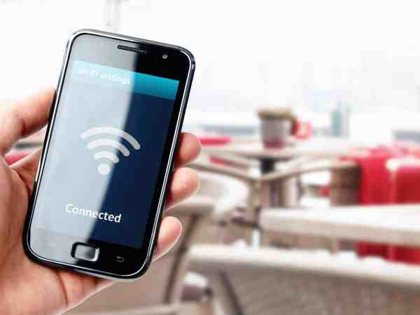 Hand holding smartphone with wi-fi connection on the screen in cafe