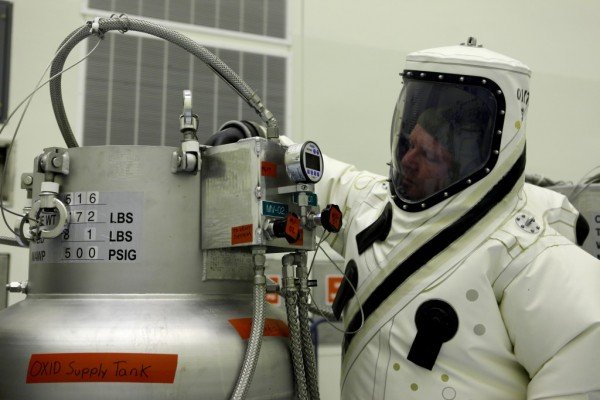 Wearing a self-contained atmospheric protective ensemble, or SCAPE, suit, Kennedy Space Center engineer Kevin Abbott opens a supply tank flow source of highly toxic and corrosive nitrogen tetroxide propellant for the system flow test. Image Credit: NASA