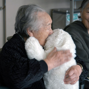 senior citizen hugs fluffy puppy. majorlt adorable.