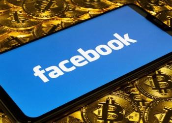 Gold Bitcoin coins pile with the Facebook logo on smartphone screen.