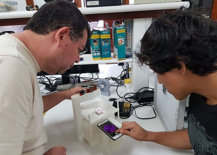 Mirko Zimic and student using their 3D printed inverted microscope linked to a smartphone