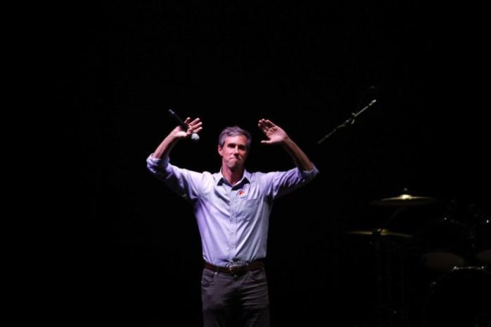 Beto O'Rourke waves to a crowd after conceding his race.