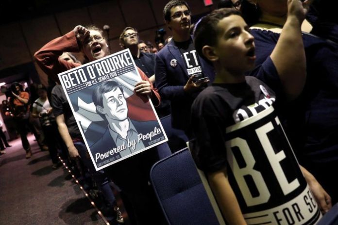 Supporters of Beto O'Rourke, then candidate for US Senate in November 2018, hold posters and cheer.