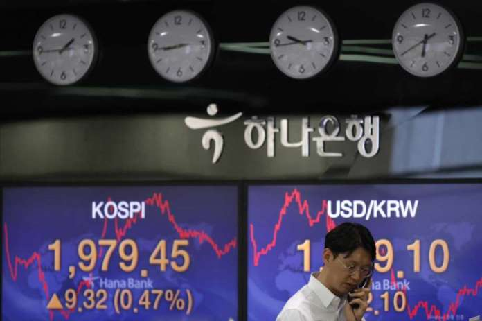 A currency trader talks on the phone near the screens showing the Korea Composite Stock Price Index (KOSPI), left, and the foreign exchange rate between U.S. dollar and South Korean won at the foreign exchange dealing room in Seoul, South Korea, Monday, May 25, 2020. Asian shares are mostly higher, with Tokyo stocks gaining on expectations that a pandemic state of emergency will be lifted for all of Japan. But shares fell in Hong Kong on Monday after police used tear gas to quell weekend protests over a proposed national security bill for the former British colony. Photo: Lee Jin-man, AP / Copyright 2018 The Associated Press. All rights reserved