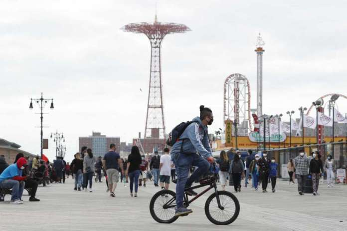 A young man wearing a protective face mask rides his bicycle along a fairly crowded Coney Island boardwalk during the current coronavirus outbreak, the afternoon of Sunday, May 24, 2020, in New York. No swimming was allowed and social distancing reminders were abundant on the beach as Memorial Day weekend kicked off the first weekend of summer. Photo: Kathy Willens, AP / Copyright 2020 The Associated Press. All rights reserved.