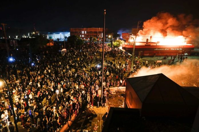 Hundreds of people stand and watch as a police station burns. The image is shot from above, and night has fallen.