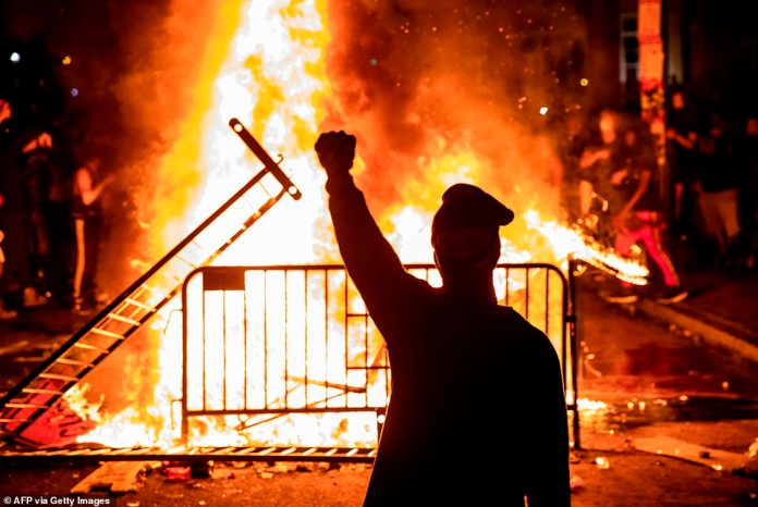 A protester raises their first near a fire outside the White House as protests engulfed the country for another night