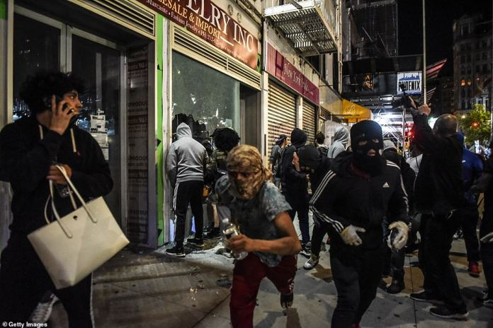 Looters in New York pictured running away from a vandalized store on Sunday evening
