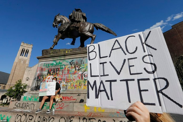 Demonstrators hold signs near the graffiti covered statue of Confederate General Stuart. Virginia Governor Ralph Northam issued a curfew for Sunday evening