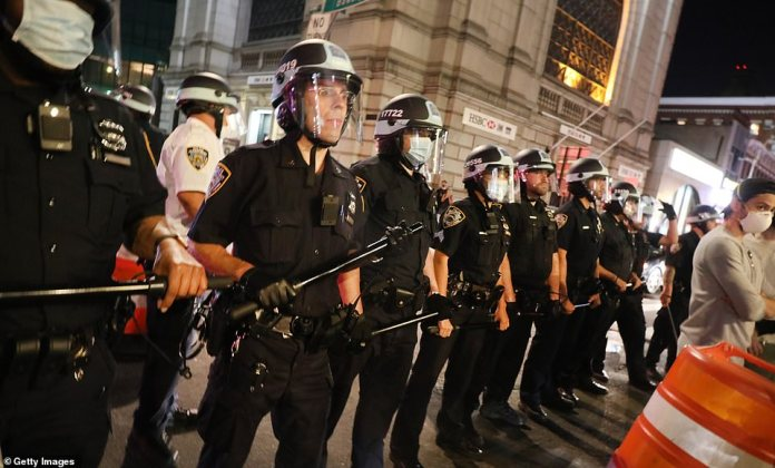 A line of police officers holding batons and wearing helmets - some of them also wearing masks - confront protesters in New York in the latest round of protests last night