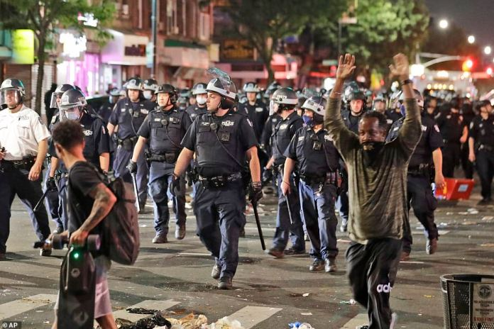 Police in riot gear walk down a street during protests in Brooklyn on Saturday night.Chiara's arrest came about an hour before de Blasio urged protesters to disperse