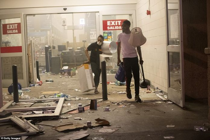 Looters pictured leaving a hardware store with lamps and merchandise in their hands after the store was raided in Sunday protests