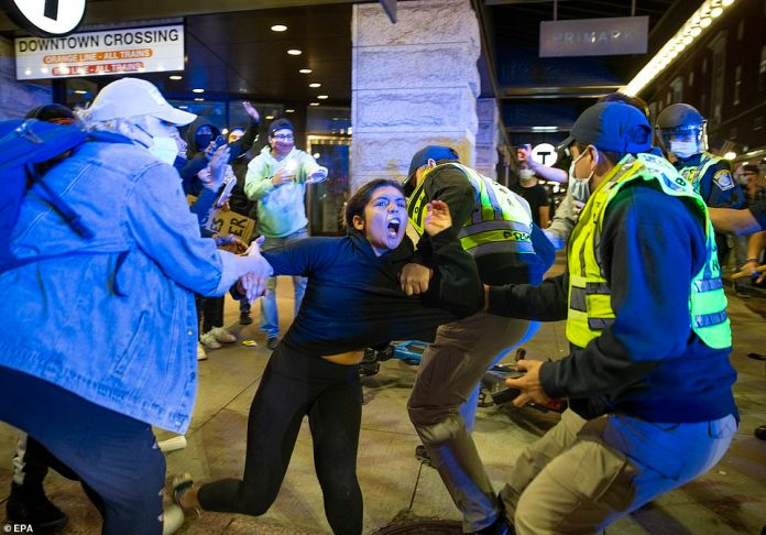 A protester pictured clashing with Boston and Massachusetts State Police on Sunday during demonstrations against the police killing of George Floyd