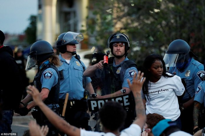 Protesters pictured being detained by officers during a rally against the death of George Floyd late Sunday
