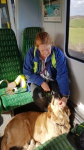 On the train; Ma sitting on green seat with Teddy lying at her feet, with his back toward her. She is tickling him under the chin and he has his head lifted up looking at her