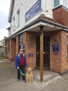 Ma and Teddy posing for a photo outside the door to Rainsbrook Vets in Rugby