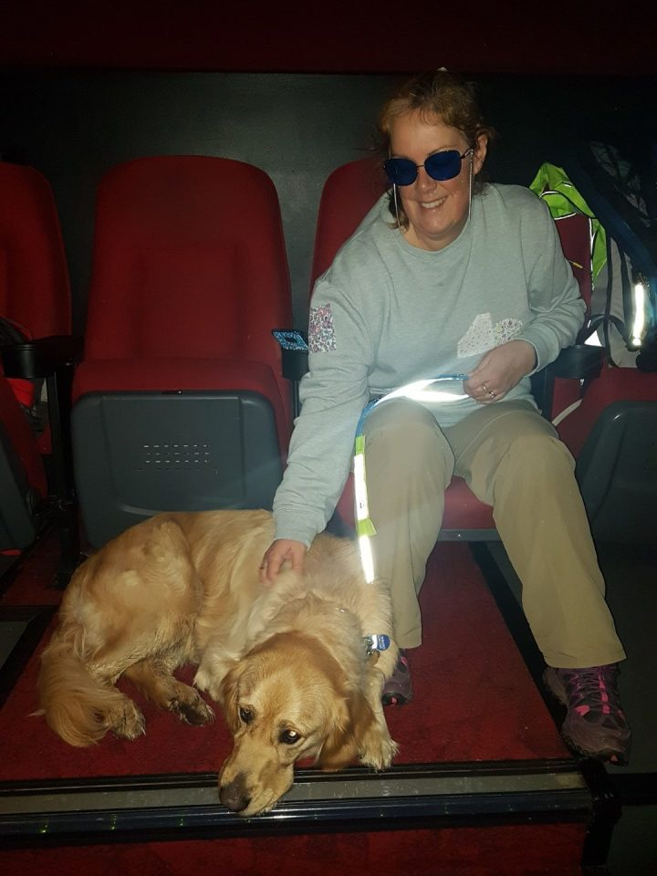 Teddy lying on red carpet beside Ma who is sat in a seat at the back of the cinema, right at the top of the steps