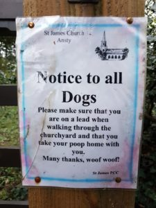 Notice on church gate post saying 'Notice to all Dogs. Please make sure that you are on a lead when walking through the churchyard and that you take your poop home with you. Many thanks. Woof Woof! '