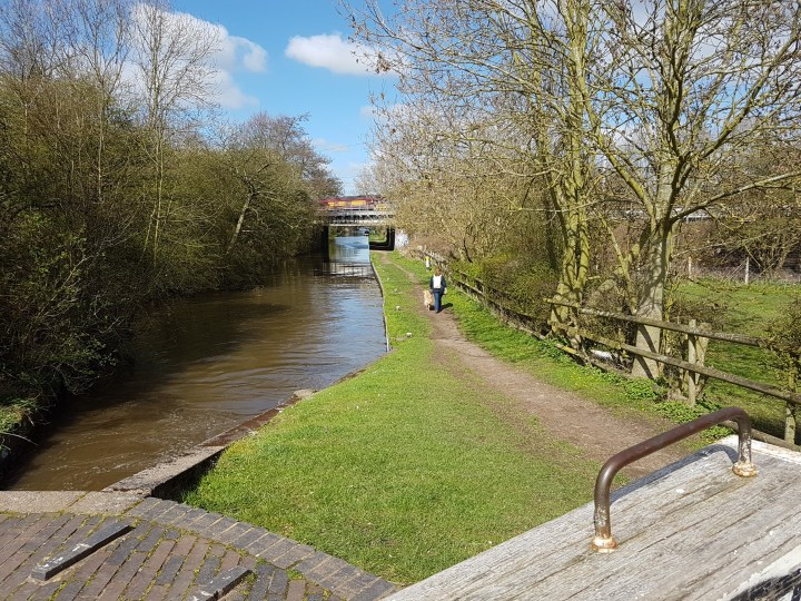 a long distance shot of the canal with towpath going down the right hand side. Mummy and Teddy are walking away into the distance. In the immediate foreground is the bricked surface of the locktop and the white end of the lockbeam with metal handle on top. There are trees lining both sides of the canal and a slightly cloudy blue sky above