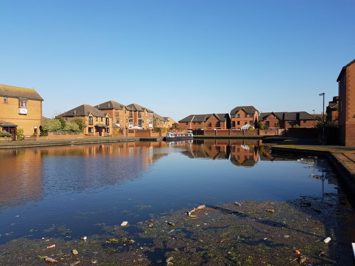 A very large canal basin amidst a housing estate. The straight-edged expanse of water is approximately the size of 2 football pitches and has a variety of styles of red brick homes around the edges. In this photo, the boat is moored in the far distance with a clear blue sky reflected in the perfectly still water. In the immediate foreground is a patch of floating rubbish.
