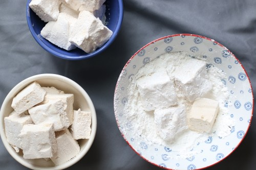 DIY marshmallows cut into large cubes and covered in powdered sugar and cornstarch