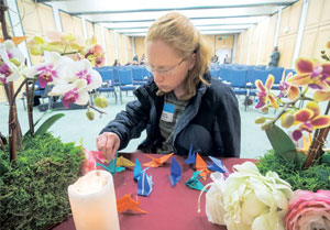 "Heidi Braunger places a note for her mother Nancy, who passed away in August 2013, during the ""A Gathering of Remembrance"" memorial service held at the Burtness Auditorium in Santa Barbara Cottage Hospital."