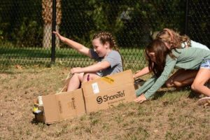 """Students testing out a """"multi-use sled"""" they built from scrap objects."""