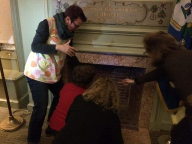 Adults searching the fireplace with a blacklight
