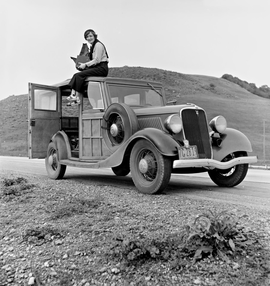 Dorothea Lange atop automobile in California.FSA photo by Rondal Partridge