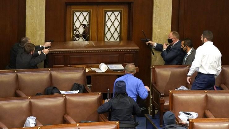 El interior del recinto de la Cámara de Representantes con una ventana rota y un grupo de fuerzas de seguridad del Capitolio apuntando sus armas a un presunto manifestante.