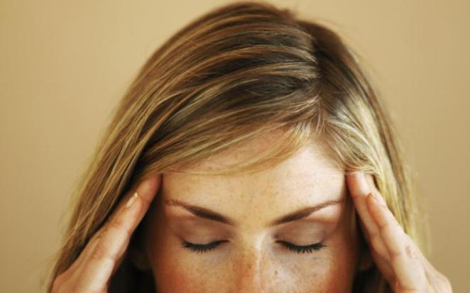 woman rubbing her head