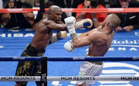 Floyd Mayweather Jr. (black trunks) and Conor McGregor (white trunks) box during the ninth round of their boxing match at T-Mobile Arena