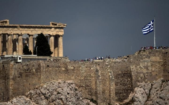 A Greek flag flutters in front of the ancient Parthenon temple