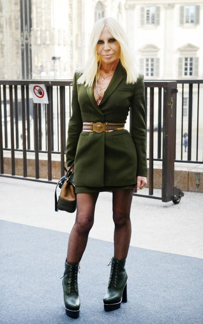 Donatella Versace wore a green mini skirt and matching suit jacket, with a belt over the top, and lace-up green stacked boots to day one of Milan Fashion Week
