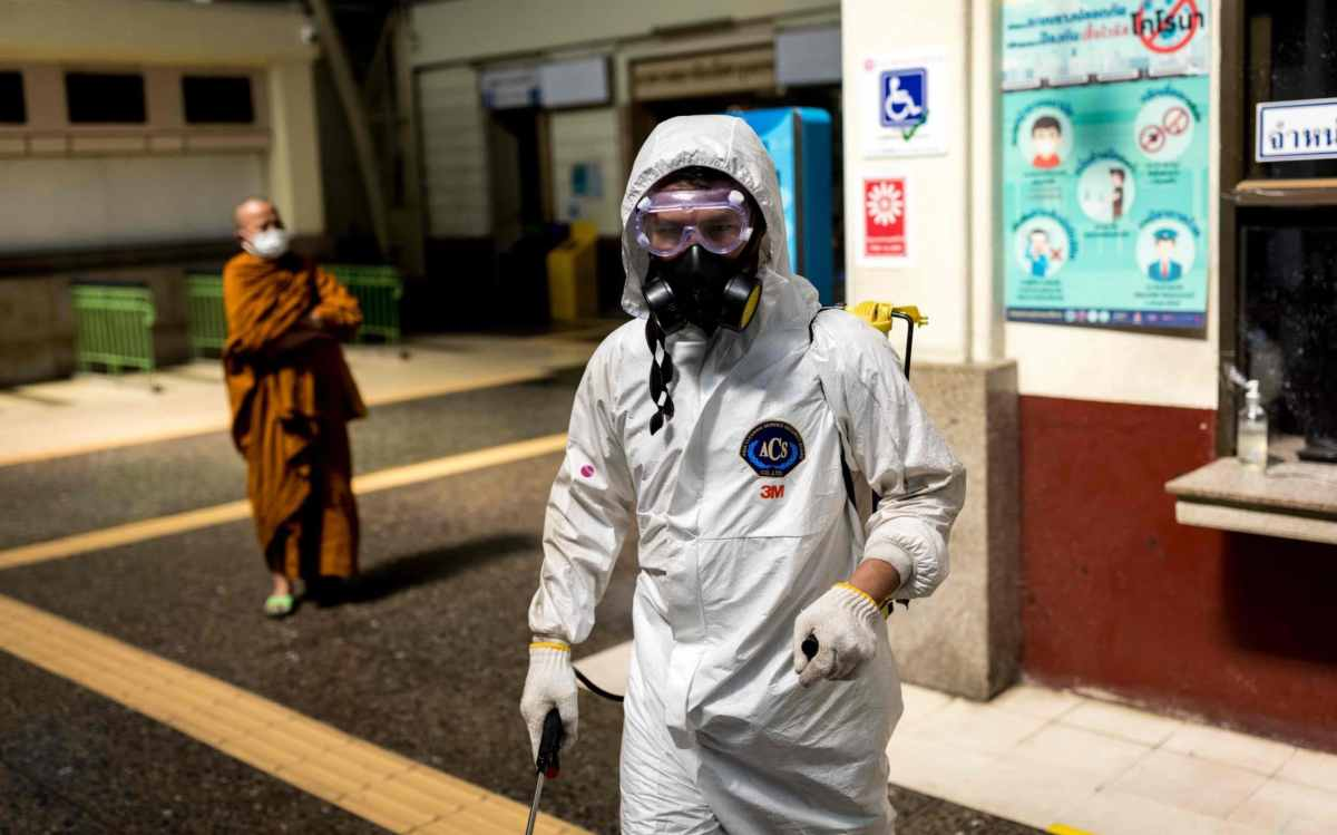 A cleaner wearing personal protective equipment disinfects Hua Lamphong railway station in Bangkok