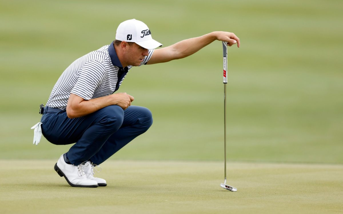 Justin Thomas of the United States lines up a putt on the 15th green in his match against Matt Kuchar of the United States