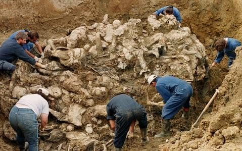 Investigators from the International War Crimes Tribunal are seen clearing soil and debris away from a large mass of compressed and decayed bodies in a mass grave in Srebrenica in 1996