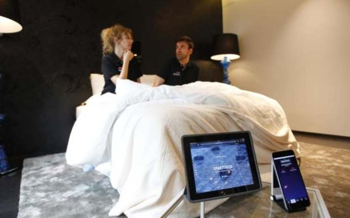 "Two people pose on the ""Smarttress"" mattress."