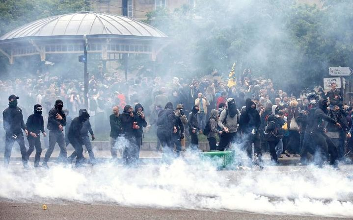 Tear gas fills the air during a demonstration in protest of the government's proposed labour law reforms in Paris