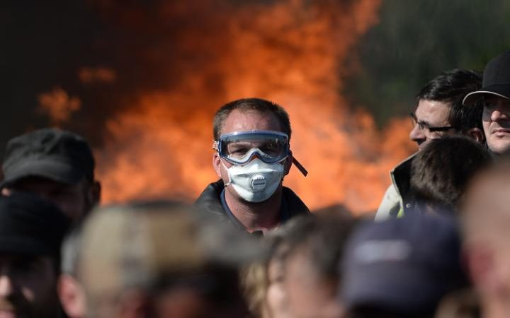 A man with a mask is pictured as workers on strike are evacuated by riot policemen as they block the access to an oil depot near the Total refinery of Donges, western france